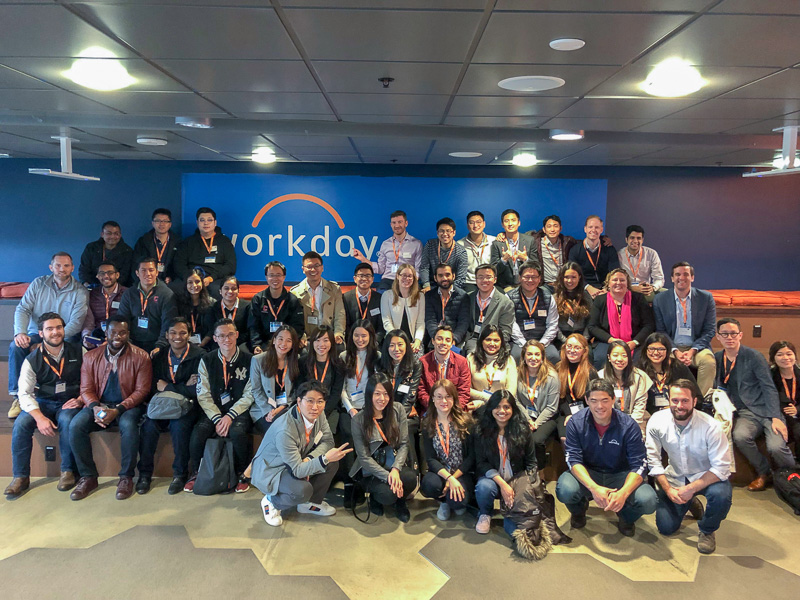 A large group of students in front of the Workday sign