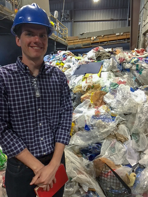 Matt stands in front of a huge pile of plastic bags