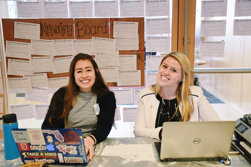 Two students sit in front of a full bulletin board
