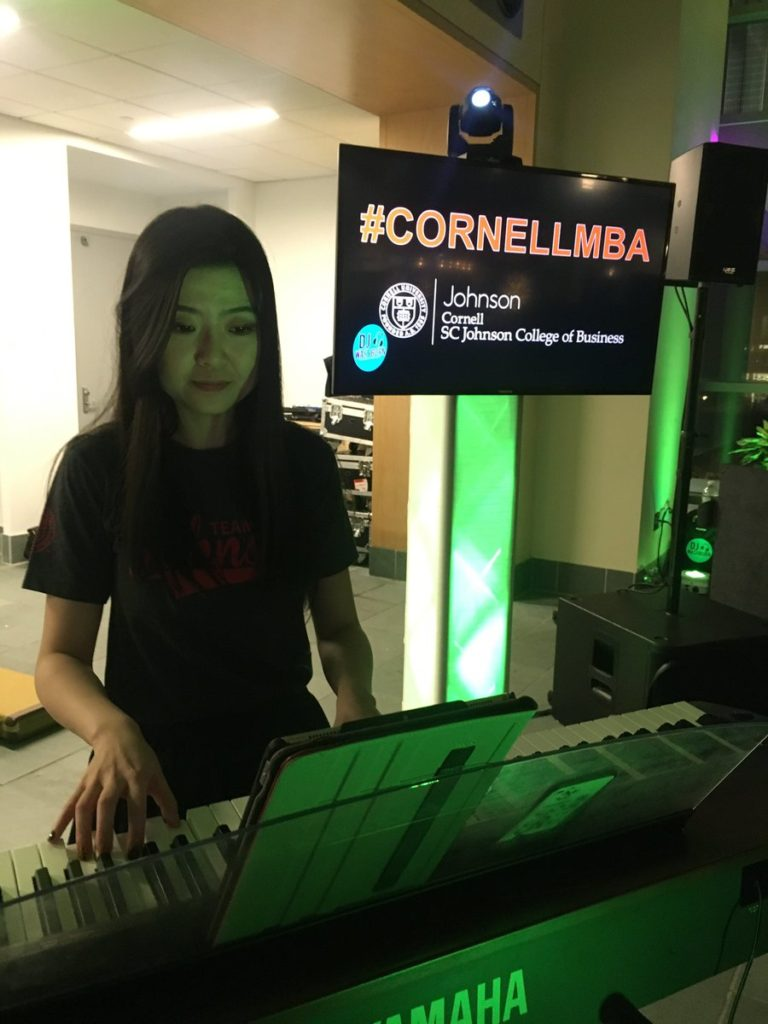 A girl plays a keyboard with #CornellMBA in the background