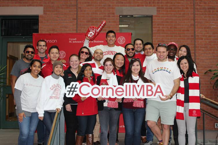 MBAs dressed in Cornell swag holding the #CornellMBA sign