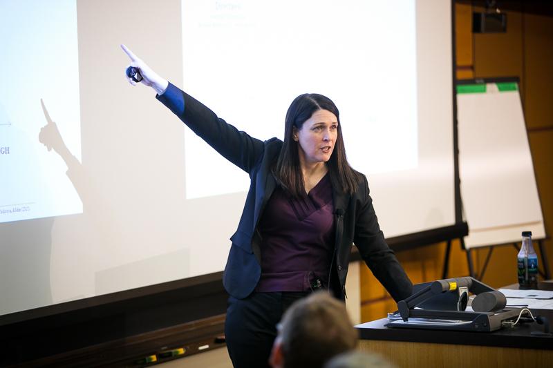 Kristin Behfar pointing to her Powerpoint presentation
