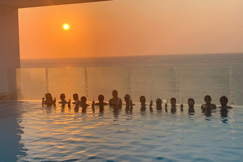 Students drinking cocktails in a pool with a sunset background