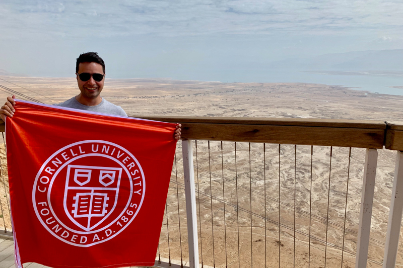 Sanchit Mall holding a Cornell banner overlooking Jerusalem