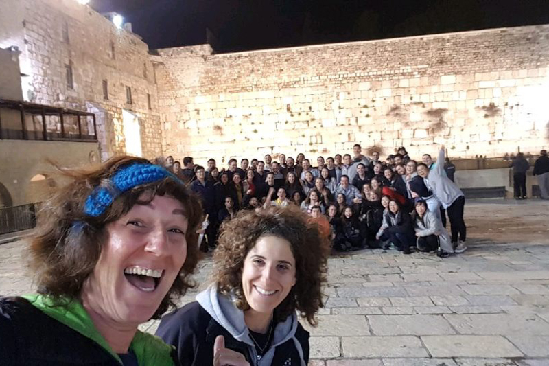 Tour guides and the group take a selfie with the Western Wall