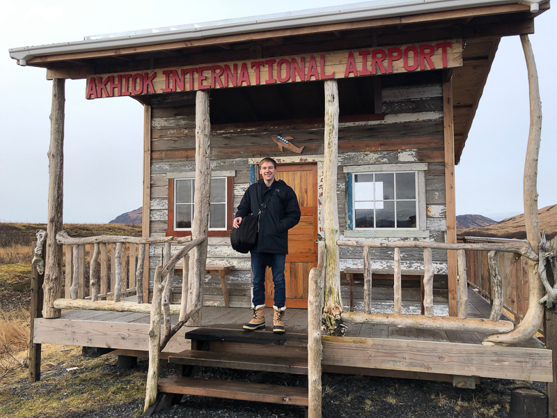 "Colin standing in front of a small building that says ""airport"""