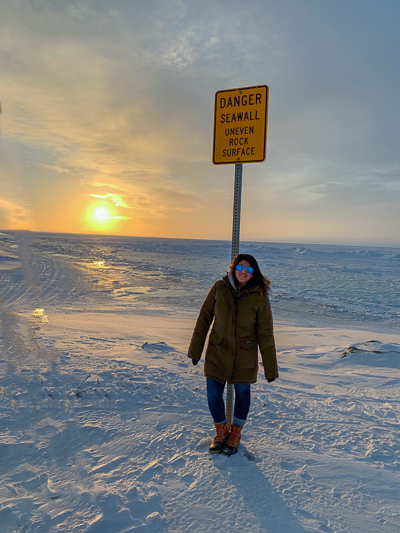Simarn standing on the snow in a the sunset