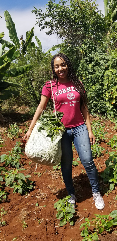 Naudia holding a bag in the farm