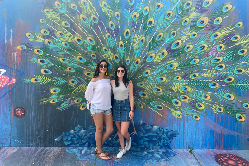 Two women standing in front of a peacock mural