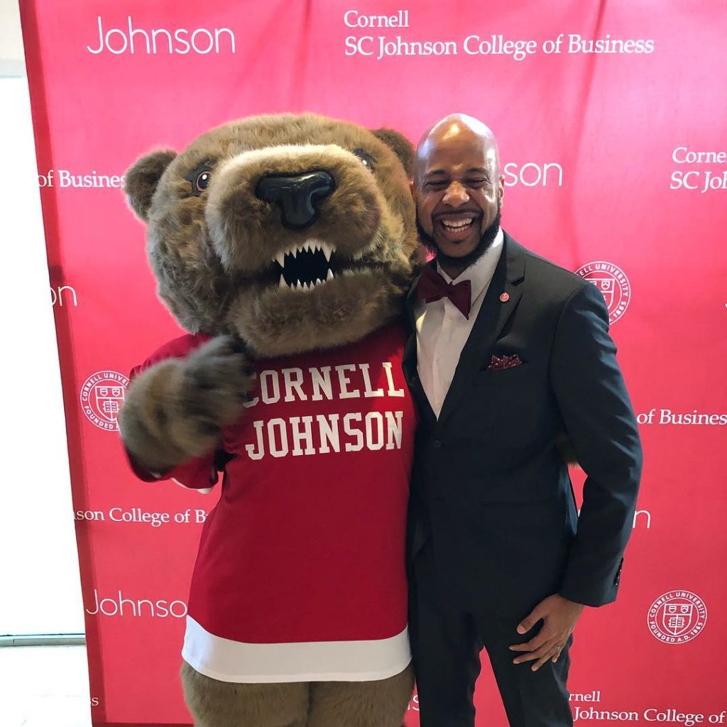 Joshua stands smiling with Touchdown at the Big Red Bash