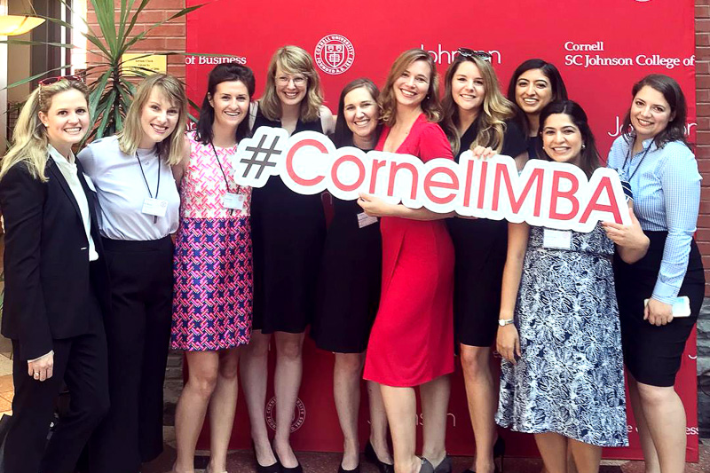 Group of women holding a Cornell MBA sign