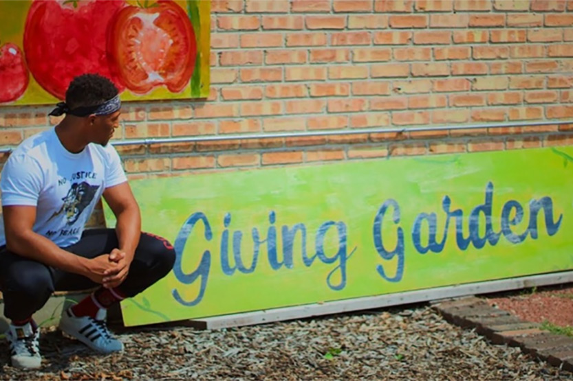 Marquan Jones next to a Giving Gardens sign