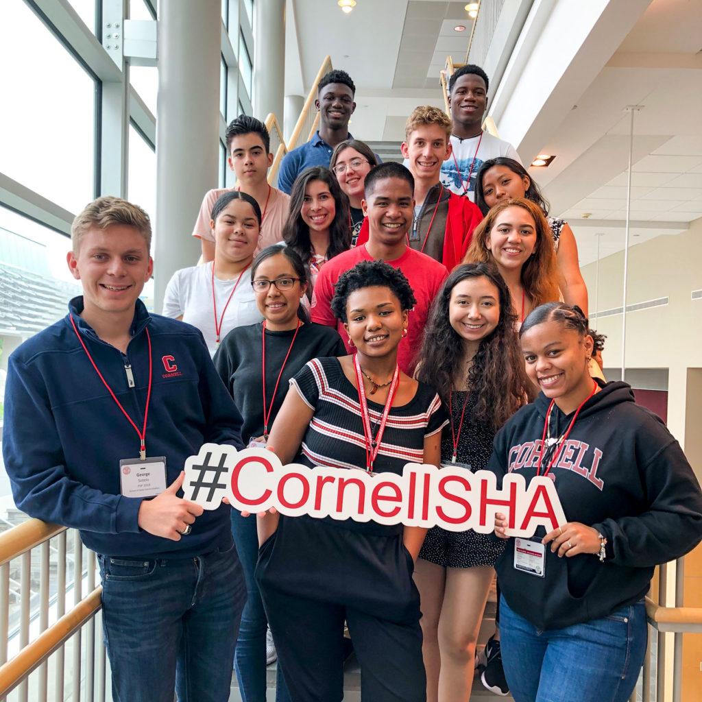 Students holding a #CornellSHA banner