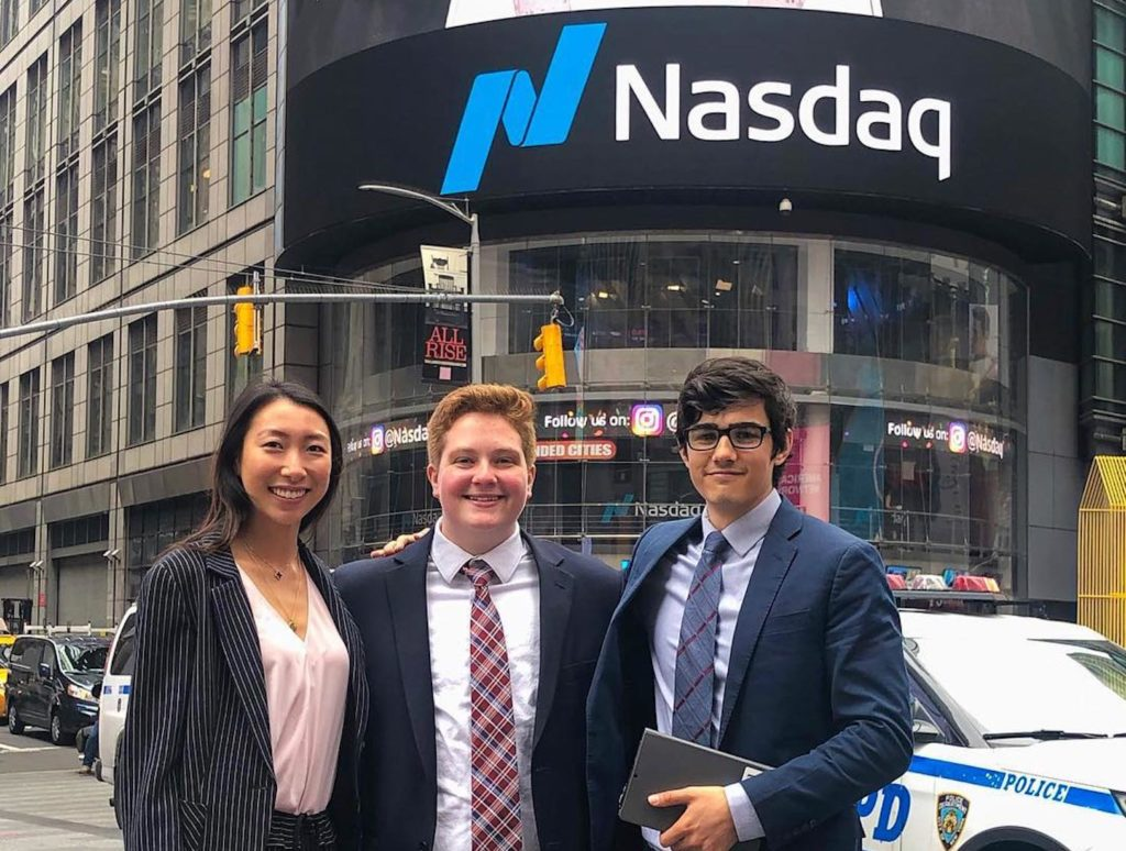 Three Hotelies stand in front of the Nasdaq building