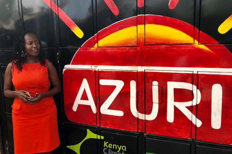 Tei Mukunya standing next to a painting of Azuri Health's logo