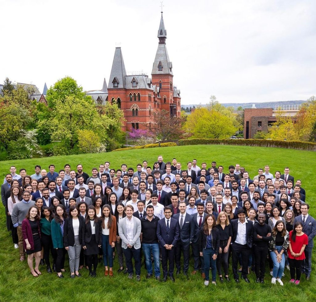 Large group of the Two-Year MBA class stands on the lawn in front of Sage Hall