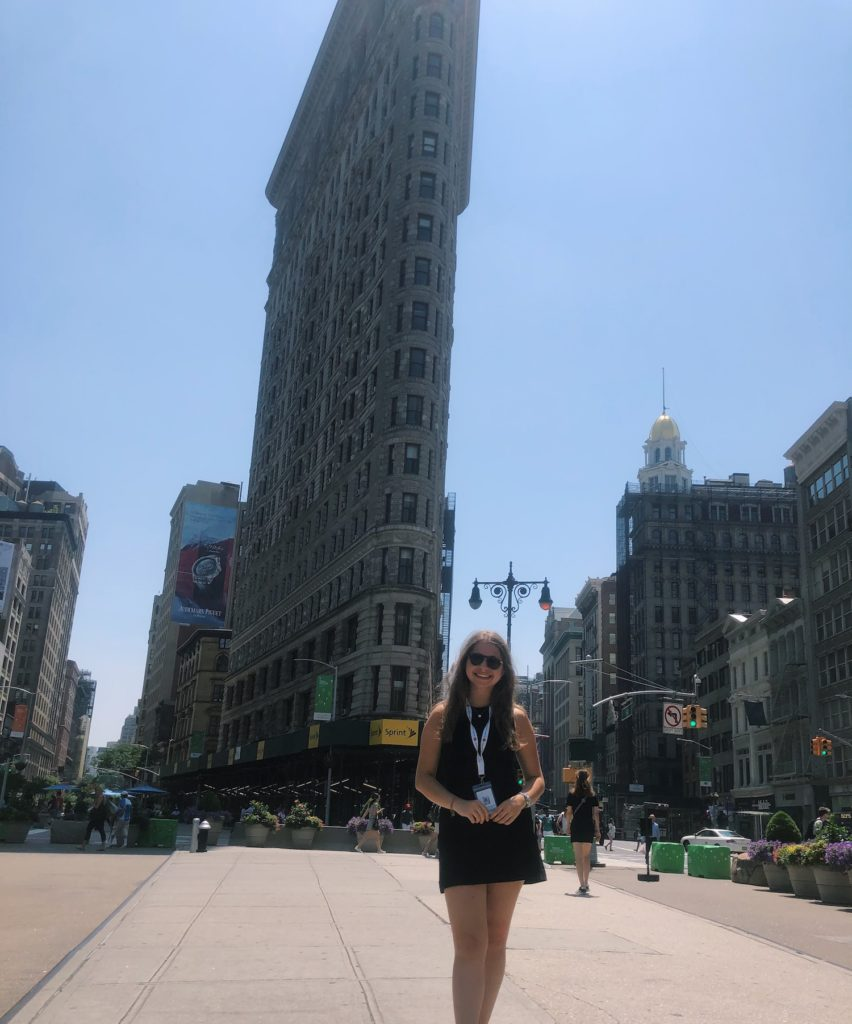 Carly standing outside the tall Eataly buidling