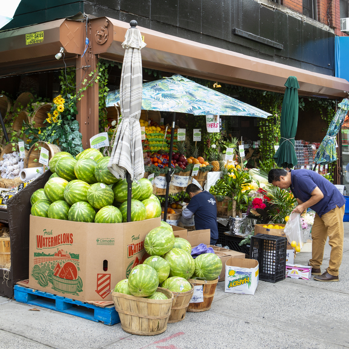 Man buying lemons at a neighborhood market in NYC
