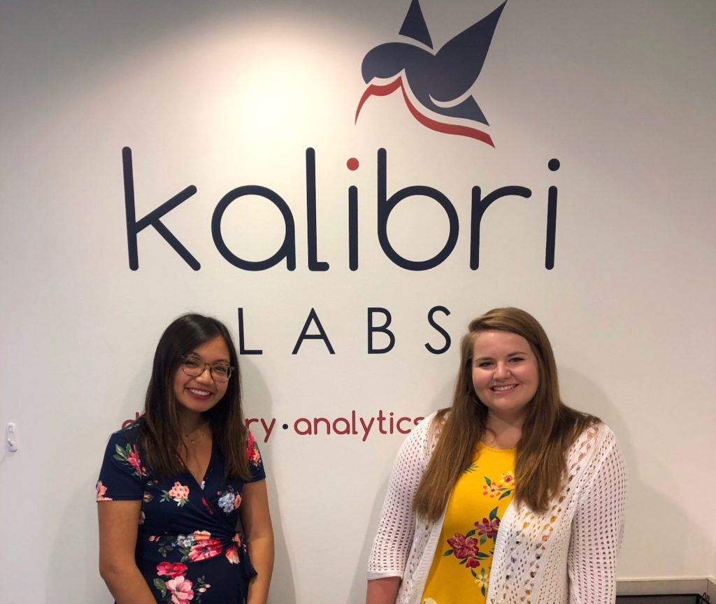 Michelle and Kristen standing in front of the Kalibri logo