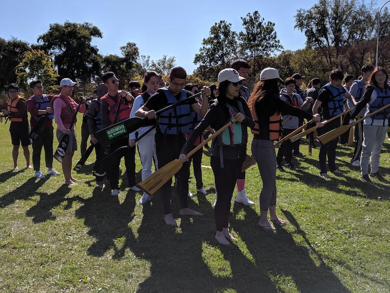 Students standing on land holding oars