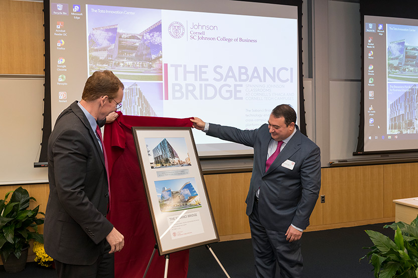 Dean Mark Nelson and Demir Savanci unveiling a framed, commemorative gift of appreciation that includes photos of the Tata Innovation Center and the Breazzano Family Center for Business Education.
