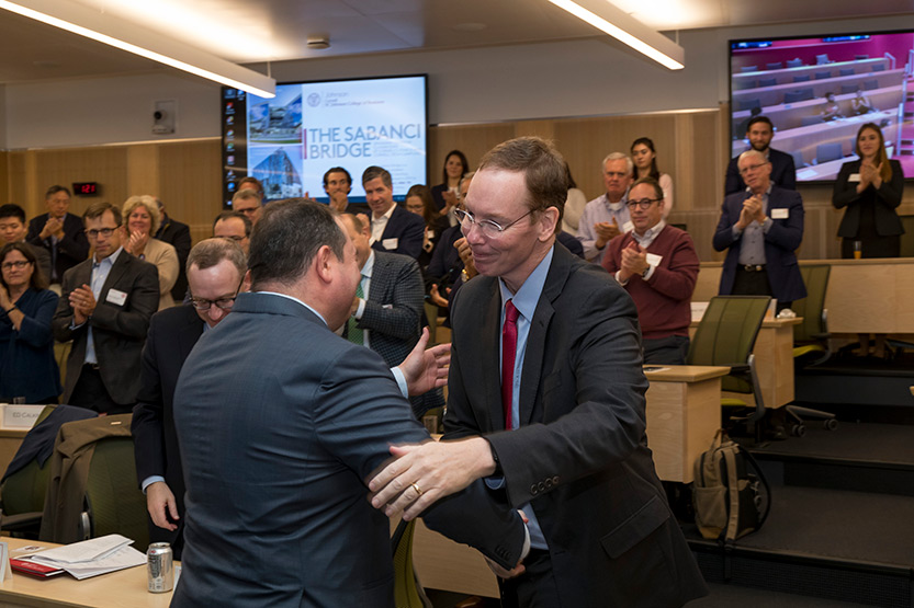 Dean Mark Nelson shaking hands with Demir Sabanci, MBA '99, at the Sabanci Bridge dedication, Oct. 21, 2019. Members of the Johnson Advisory Council are seated in the background.