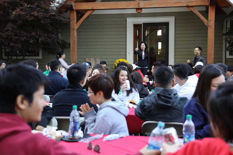 Ya Ru speaks to students seated at tables in her yard
