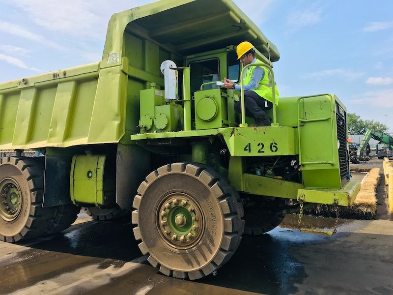 Nikunj sitting in a large green truck