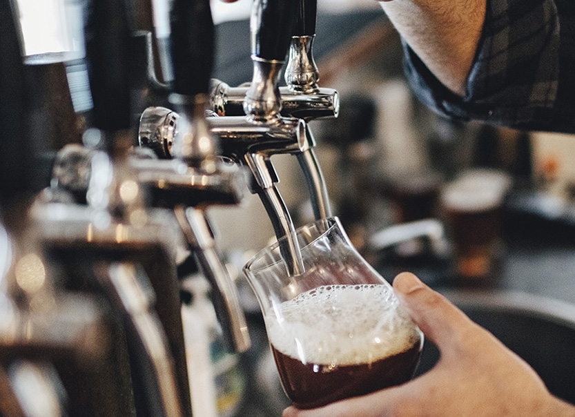 Hand holding a glass and pouring beer in a row of beer taps.