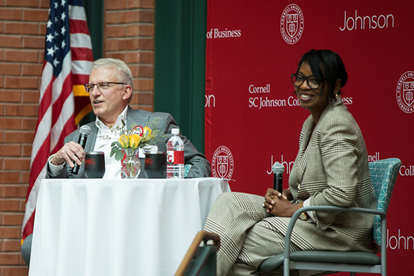 Larry Ruff, MBA '82, and Cynthia Saunders-Cheatham seated at a table on stage in Sage Hall's Dyson Atrium