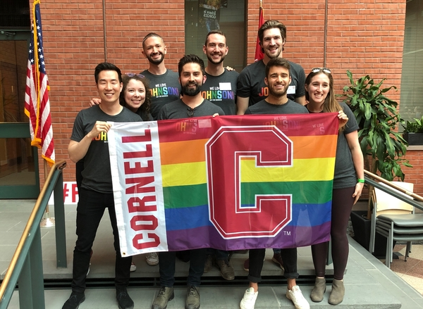 2019 O4B leadership team with Cornell Pride flag at the Out for Business Pride! Sage Social.