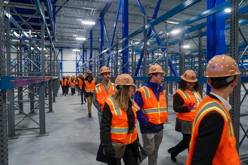 Students tour a building with hard hats
