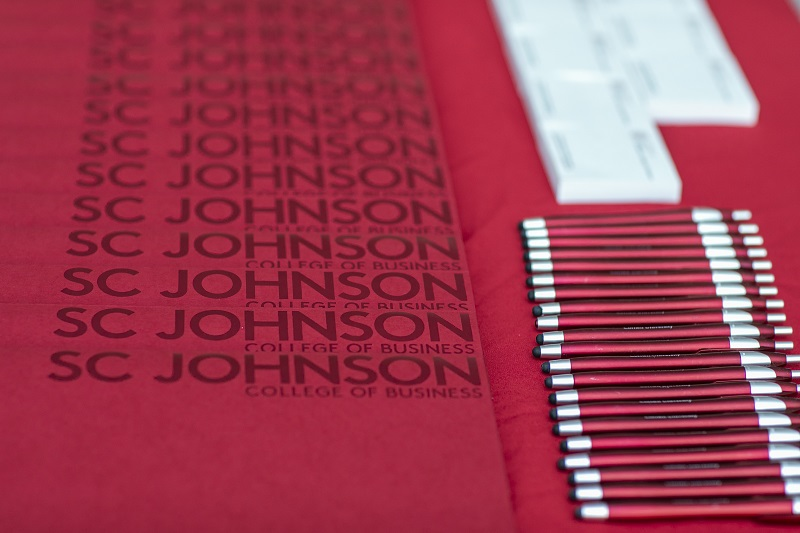 Pens, folders, and small note pads with the SC Johnson College of Business logo lie on a table.