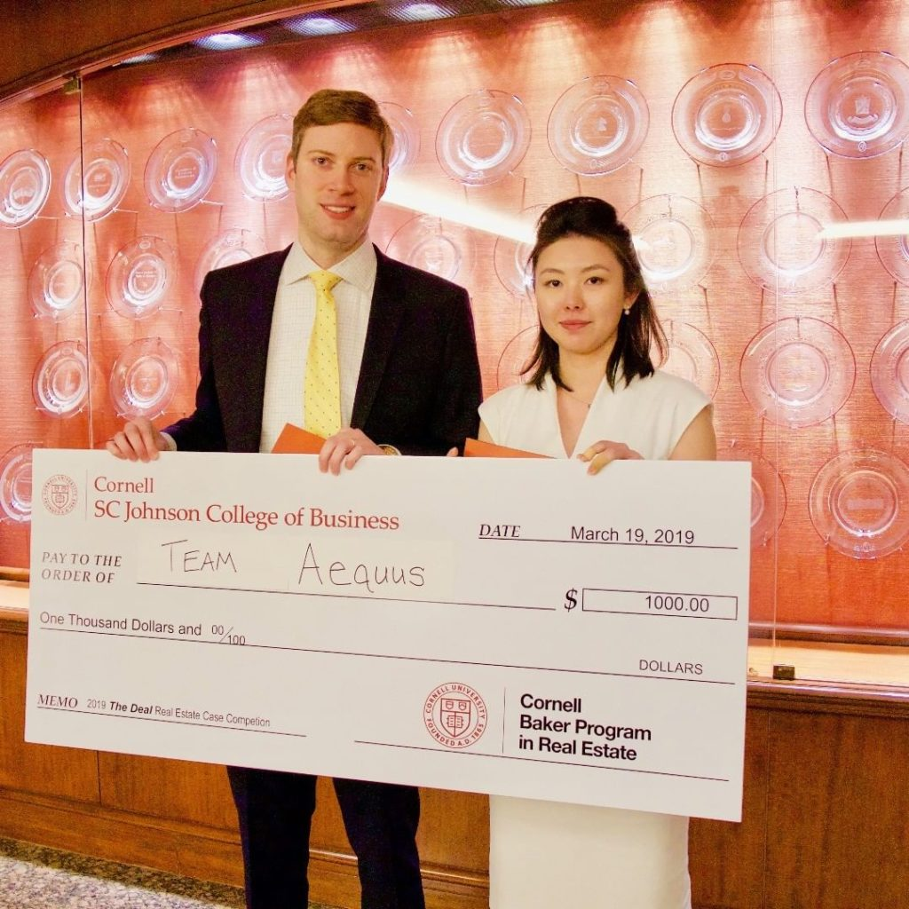 Two students holding an oversized check for $1,000