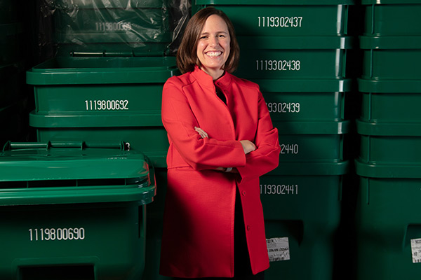 Christina Keller standing in front of a stack of green plastic bins