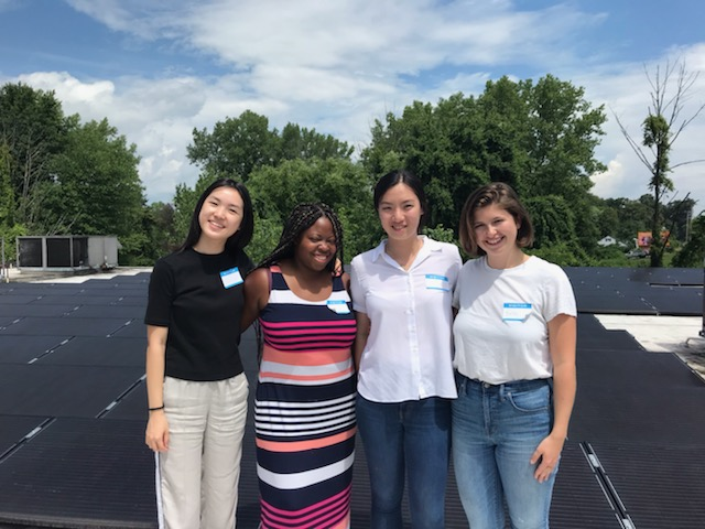 Four women standing on top of solar panels on a roof.