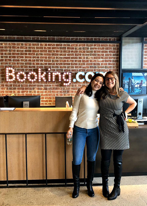 Emma Brett and Cassandra Martinez stand in front of the Booking.com company sign.