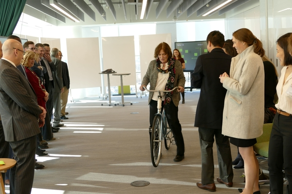 Linda Canina rides a bike in a demonstration at Deloitte