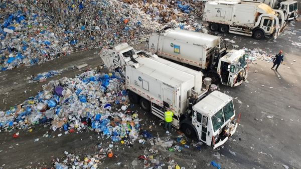 Trucks dumping piles of recycling