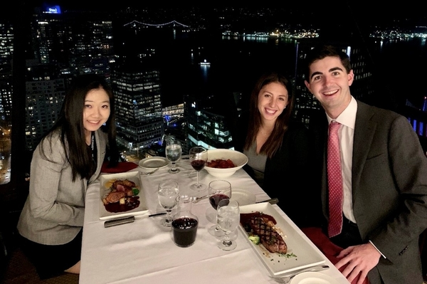 : Carol Wang, Tori Weissman, and Tim Bergin sit at restaurant table with Vancouver skyline at night behind them.