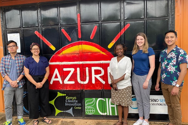 Five people stand around a sign that says Azuri