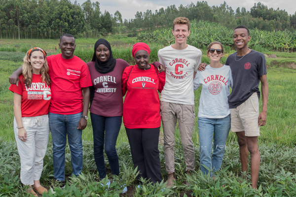 A group of people wearing Cornell attire pose in a field