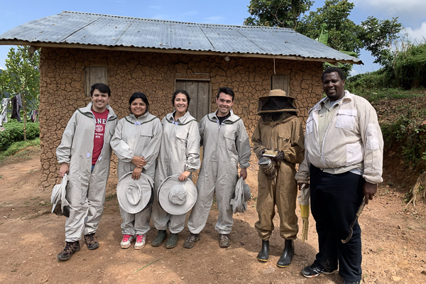 A group standing outside wearing beekeeping gear