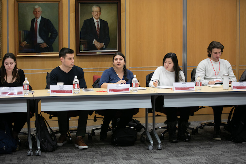 Four students sit behind a table.