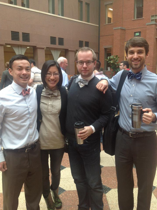 Four former students pose on campus, all wearing bow ties.