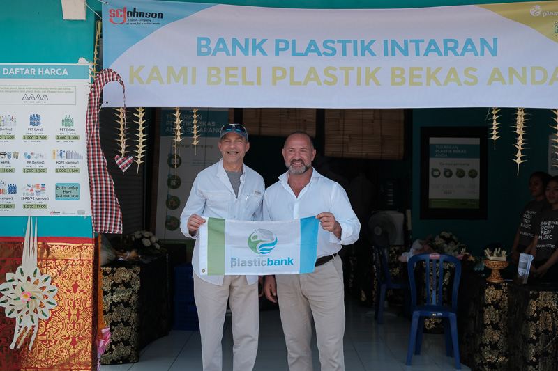 Fish and David hold a banner that says Plasticbank