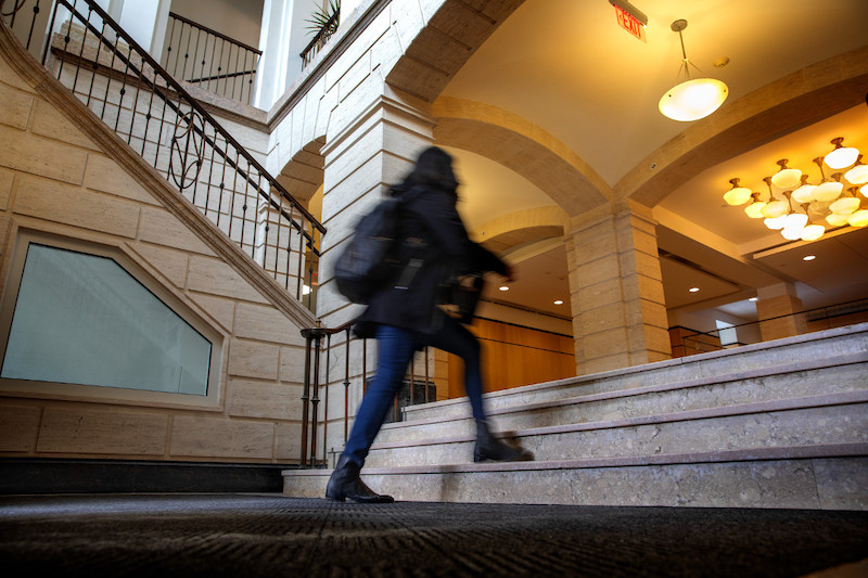 Student walking up a staircase inside Warren Hall