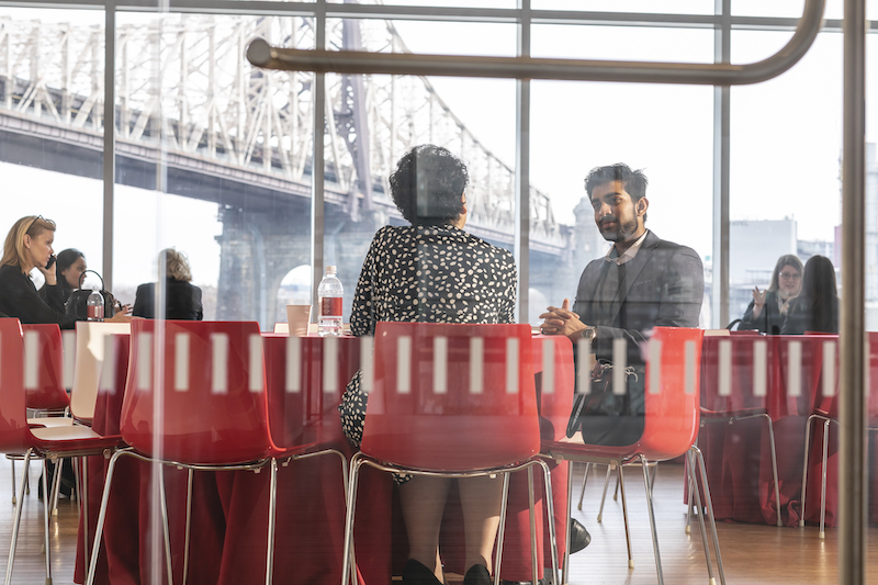 A student and mentor seated at a table in a Cornell Tech meeting space