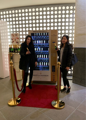 Ashleigh standing next to a wine vending machine