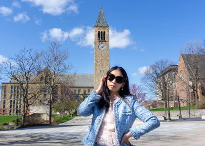 Ploy standing in front of the Cornell clock tower